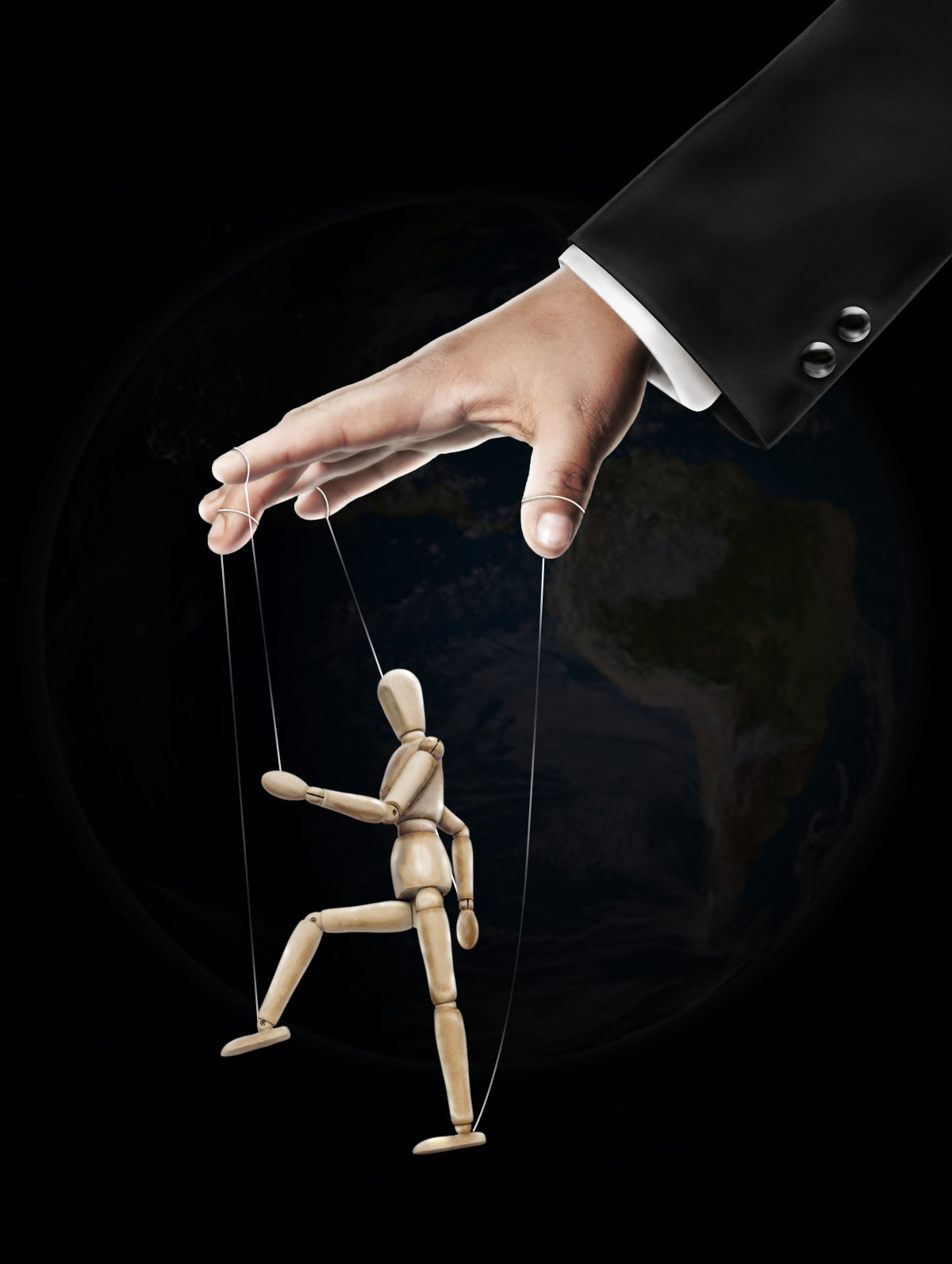 A hand emerging from a suit sleeve controlling the strings of a wooden puppet walking